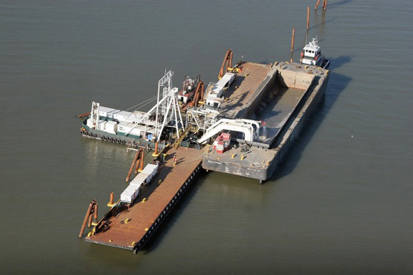 The baylands at former Hamilton Air Force Base had subsided approximately six feet below mean sea level. To raise the elevation of the marsh, a hydraulic offloader the size of a small island was used to pipe in tons of clean, dredged sediment. Tides will do the rest. Image credit: US Army Corps of Engineers