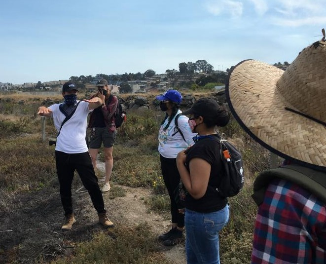 Group of people wearing masks at the edge of the estuary discussing project field work.